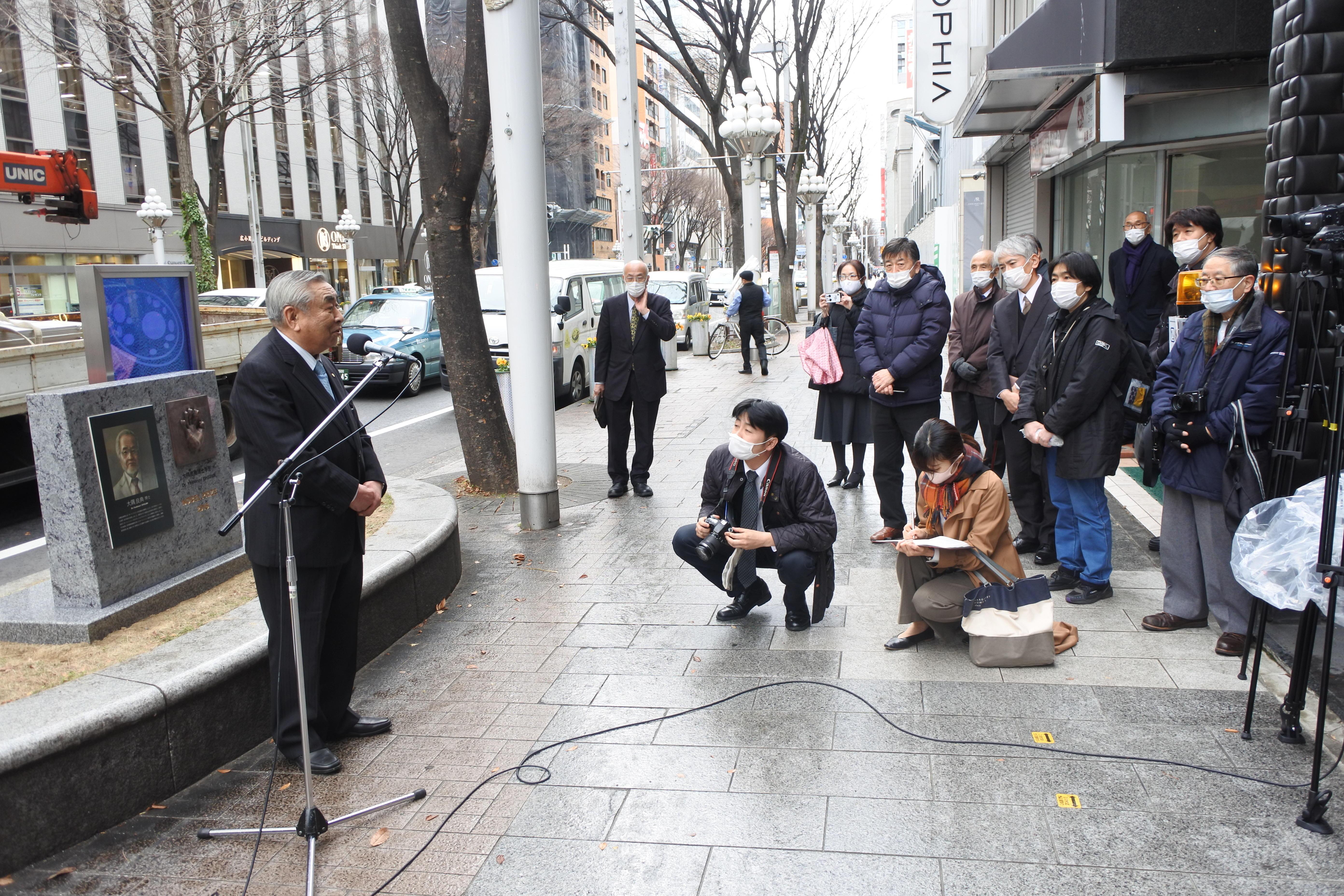 大隅良典栄誉教授の手形モニュメントの前であいさつする坪井明治理事長