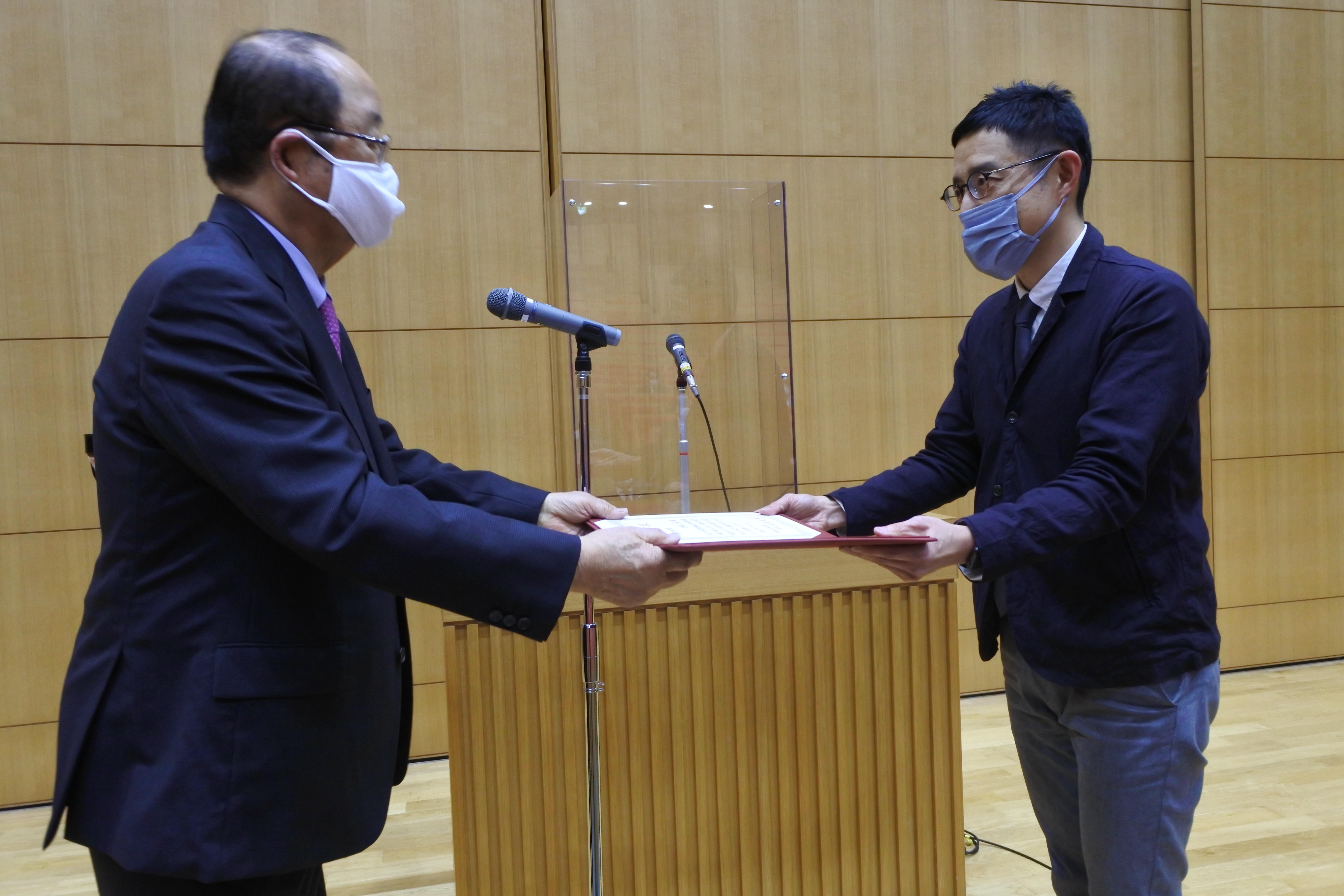 立花貞司理事長(左)から表彰を受ける谷田真准教授