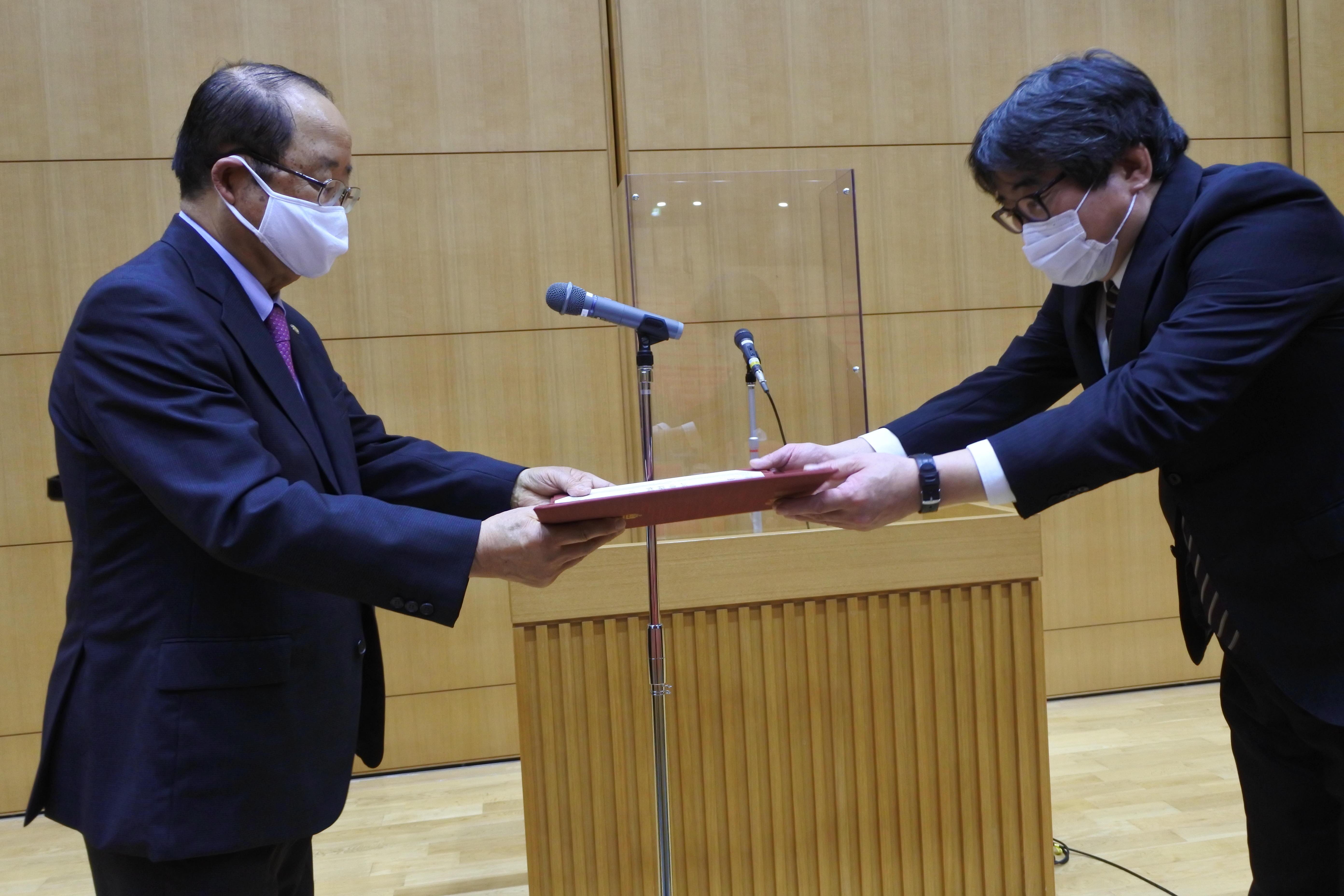 人間学部の4教授を代表して表彰を受ける宮嶋秀光教授