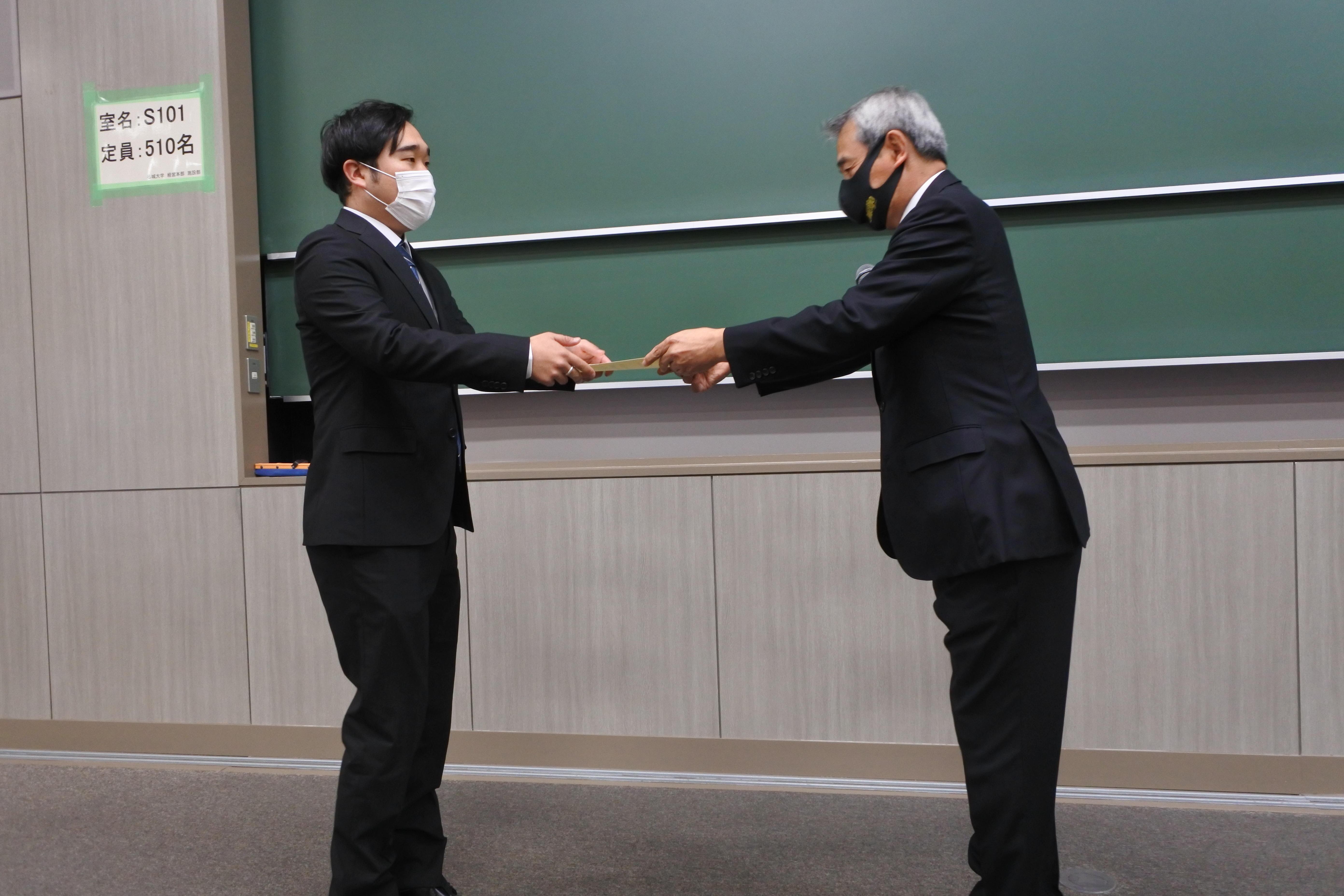 大学院理工学研究科を修了し学位記を受け取る村田優大さん(左)