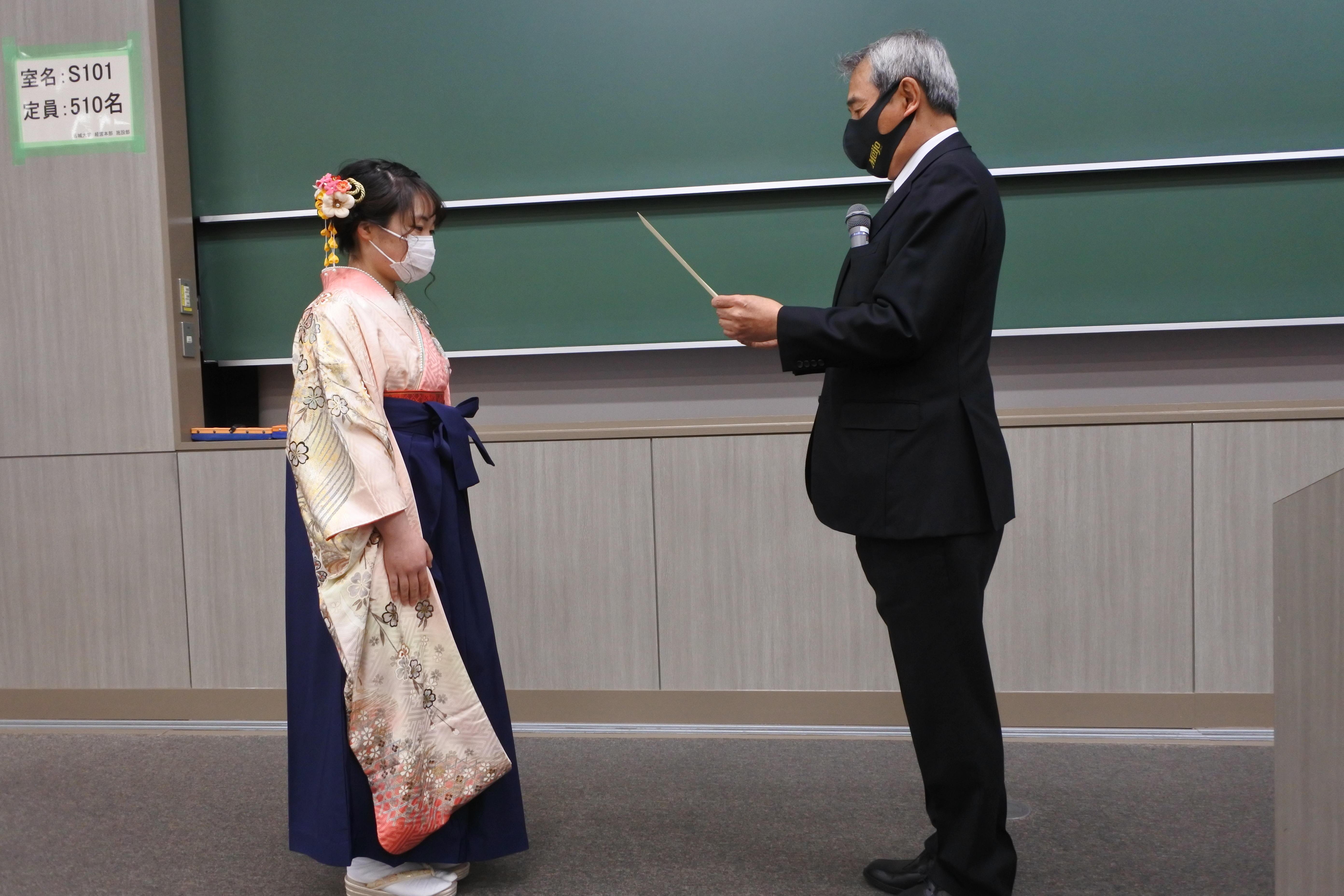 理工学部交通機械工学科を卒業し加鳥裕明学科長(右)から学位記を受け取る古川恵里奈さん