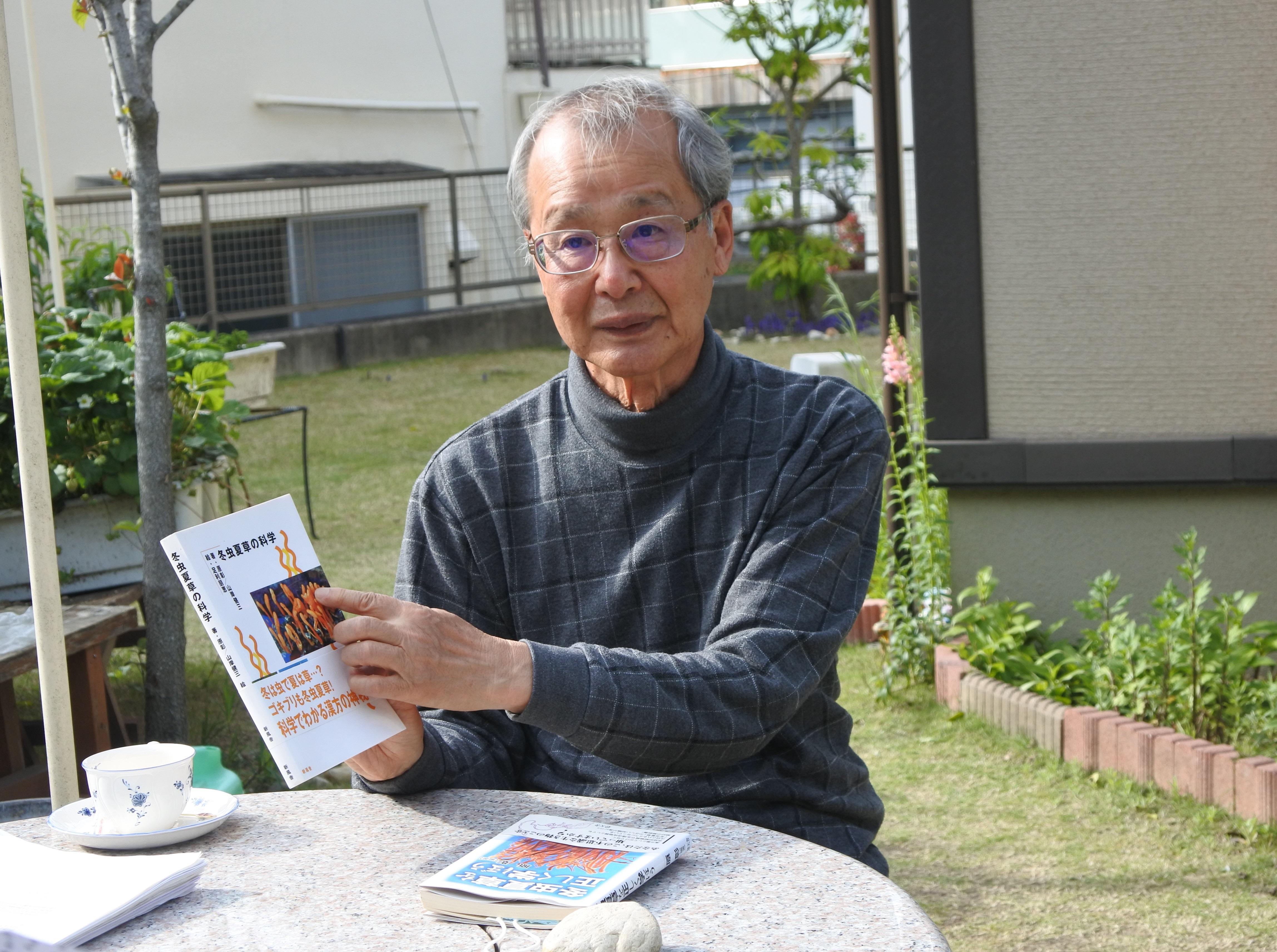 冬虫夏草に関する著書を手にする原彰名誉教授