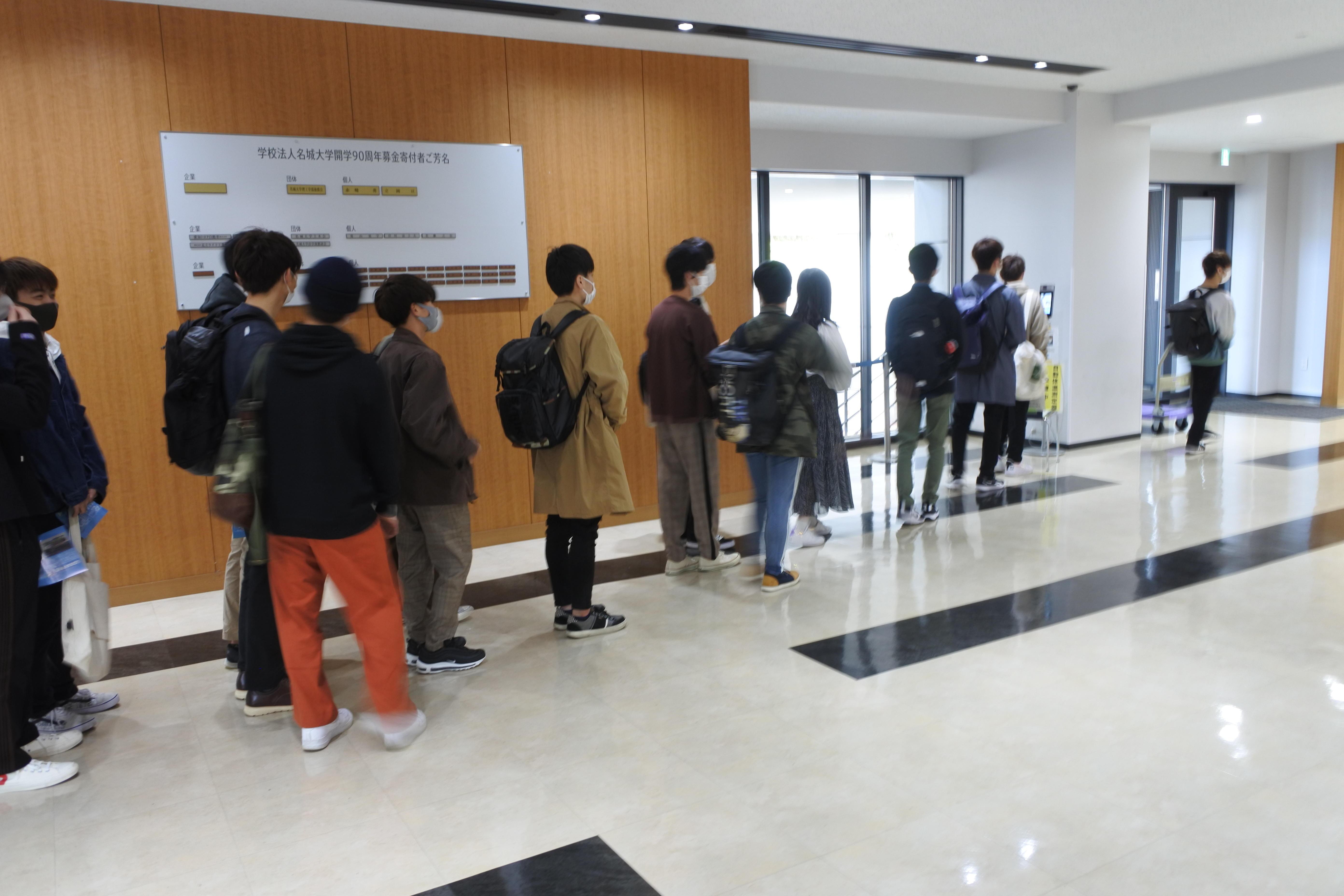天白キャンパス共通講義棟東で検温を待つ新入生の列