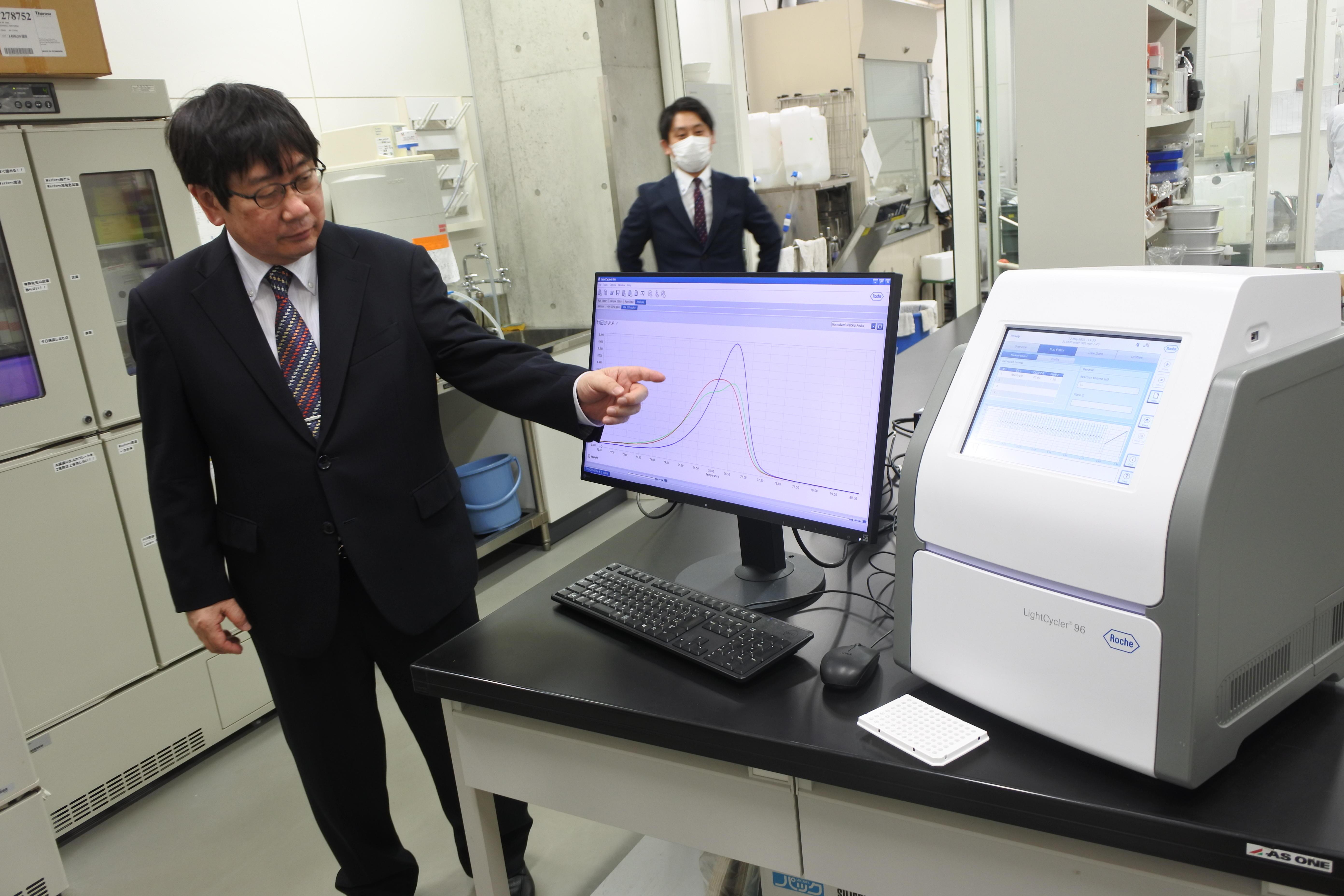 パソコン画面の融解曲線の違いを示す神野透人教授。薬学部衛生化学研究室のPCR検査装置(右)