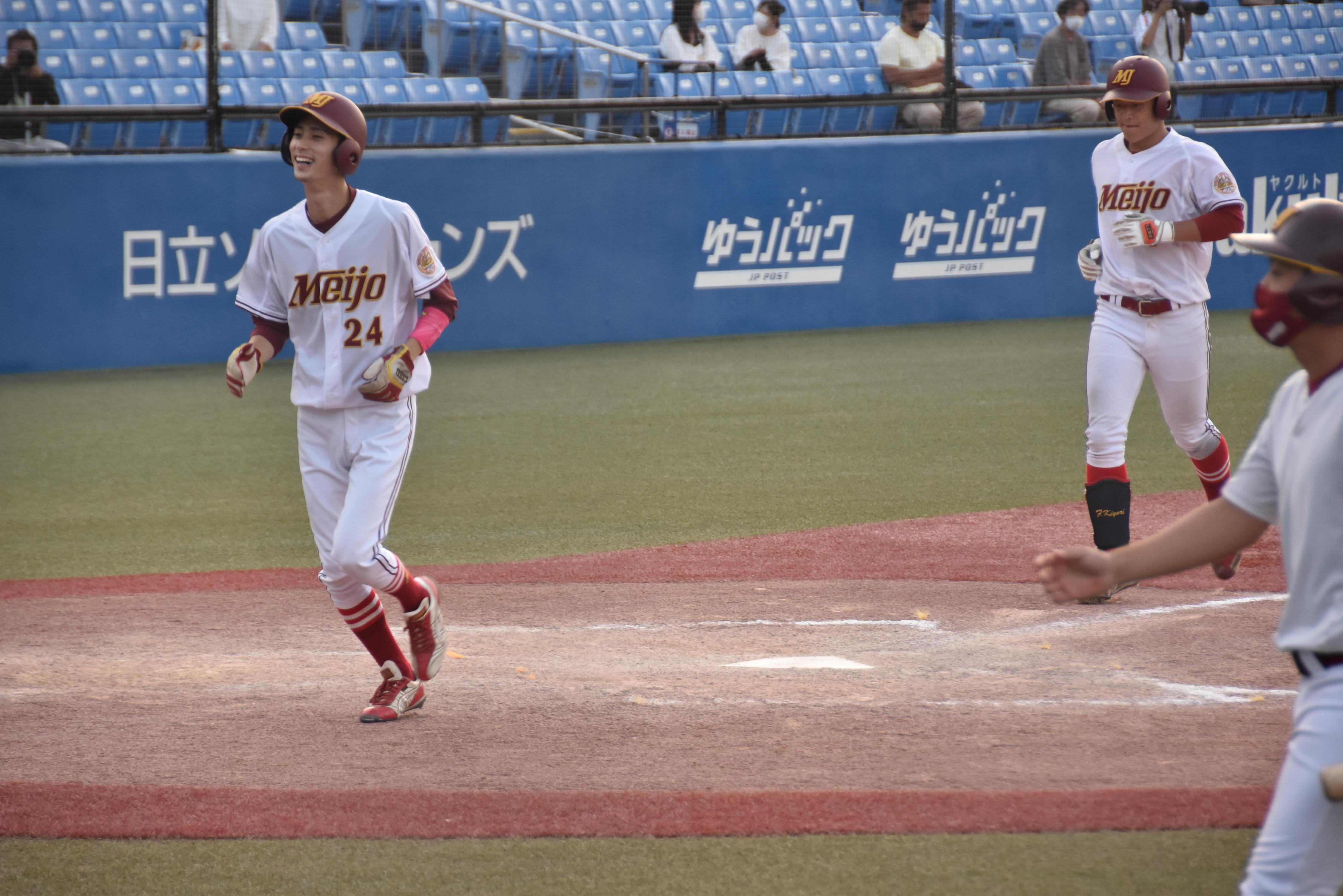 九回の追い上げ。2点本塁打を放ち、藤原連太郎選手(人間学部4年)(左、24番)に続いてホームに還る藤田希和選手(法学部3年)=東京の神宮球場で