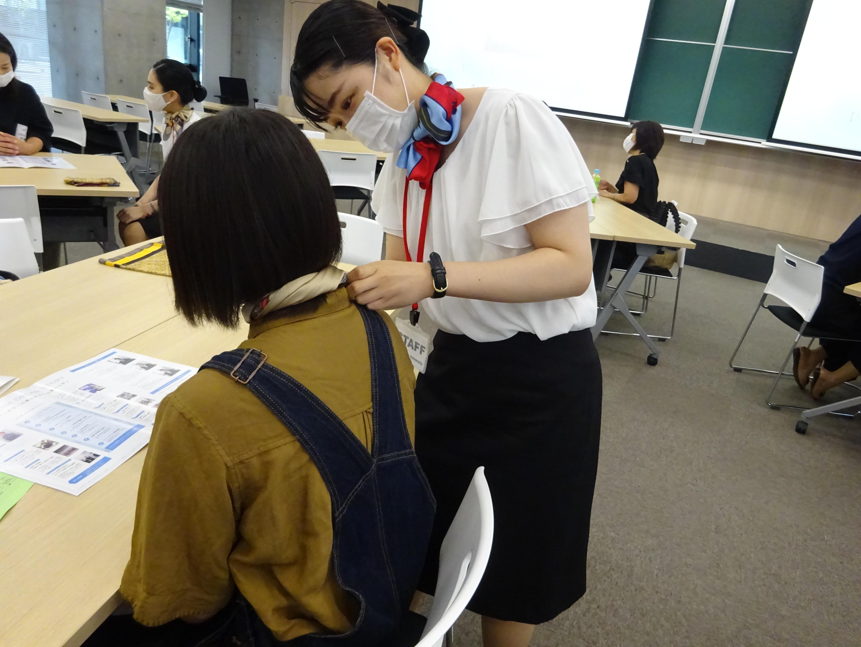 遠方から飛行機で来てくれた高校生にスカーフを巻いている様子