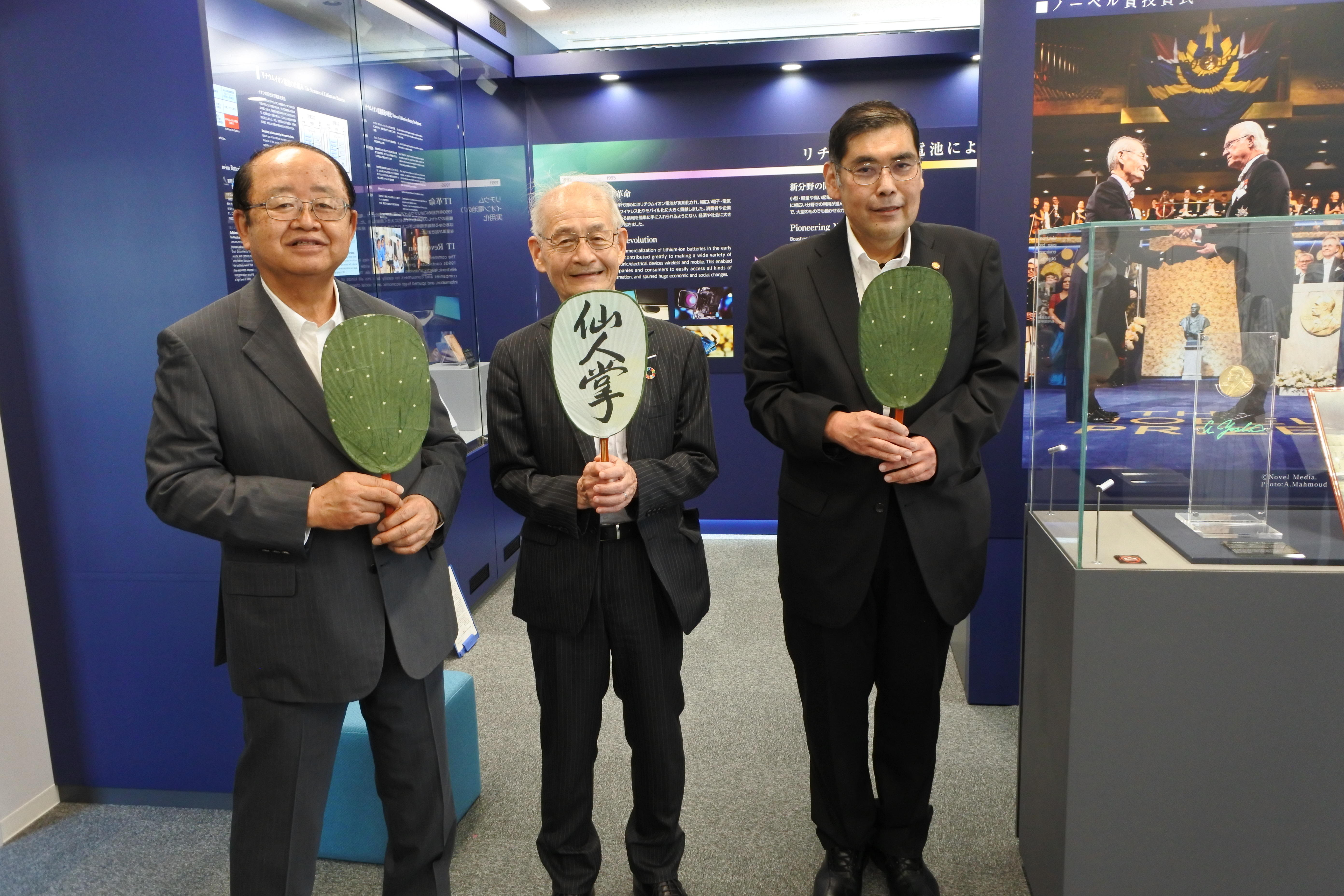 ガラスケースの脇で記念写真に納まる(左から)立花貞司理事長、吉野終身教授、小原学長
