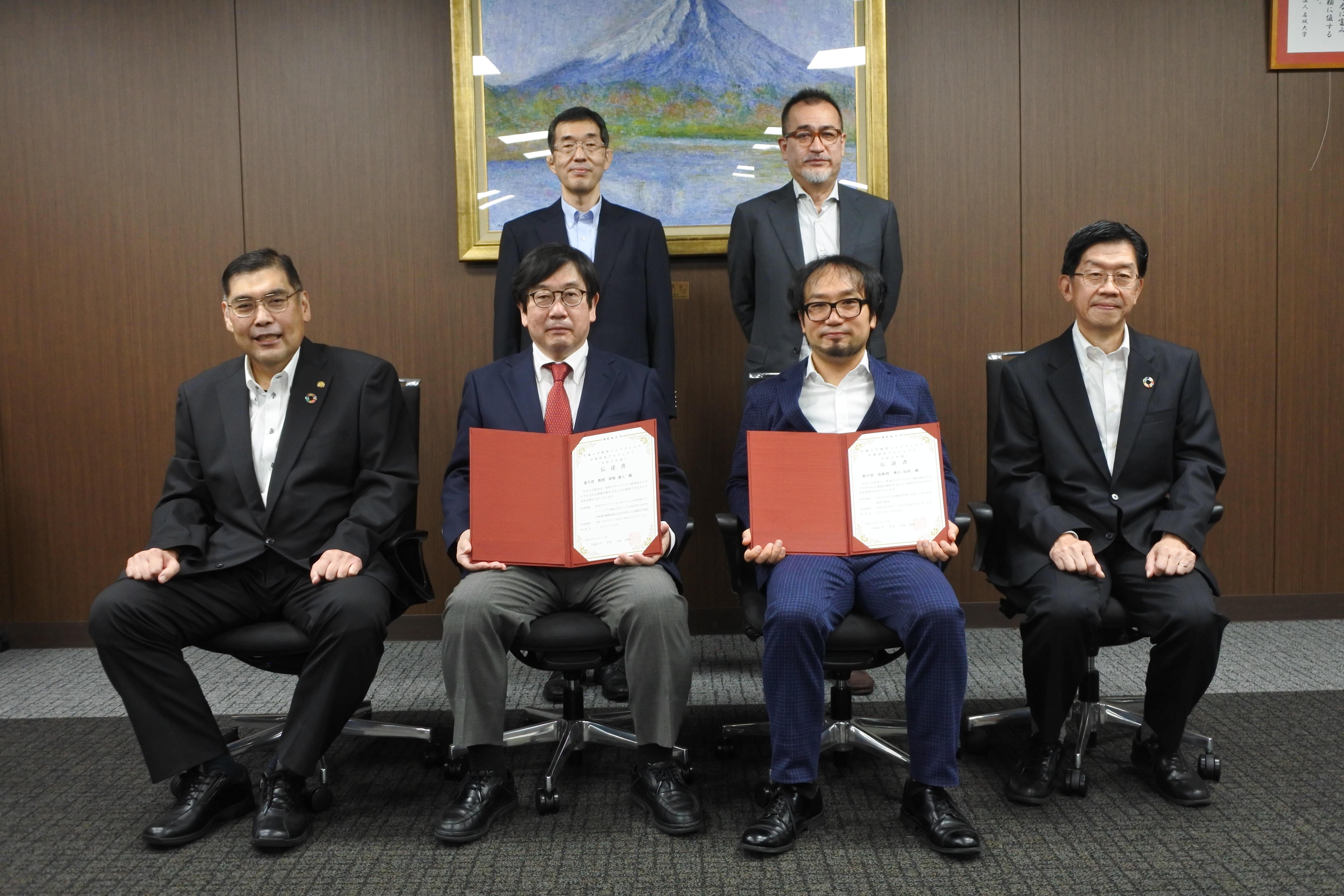 プロジェクトの伝達書を手にする神野透人教授(前列左から2人目)と奥田知将准教授(同3人目)