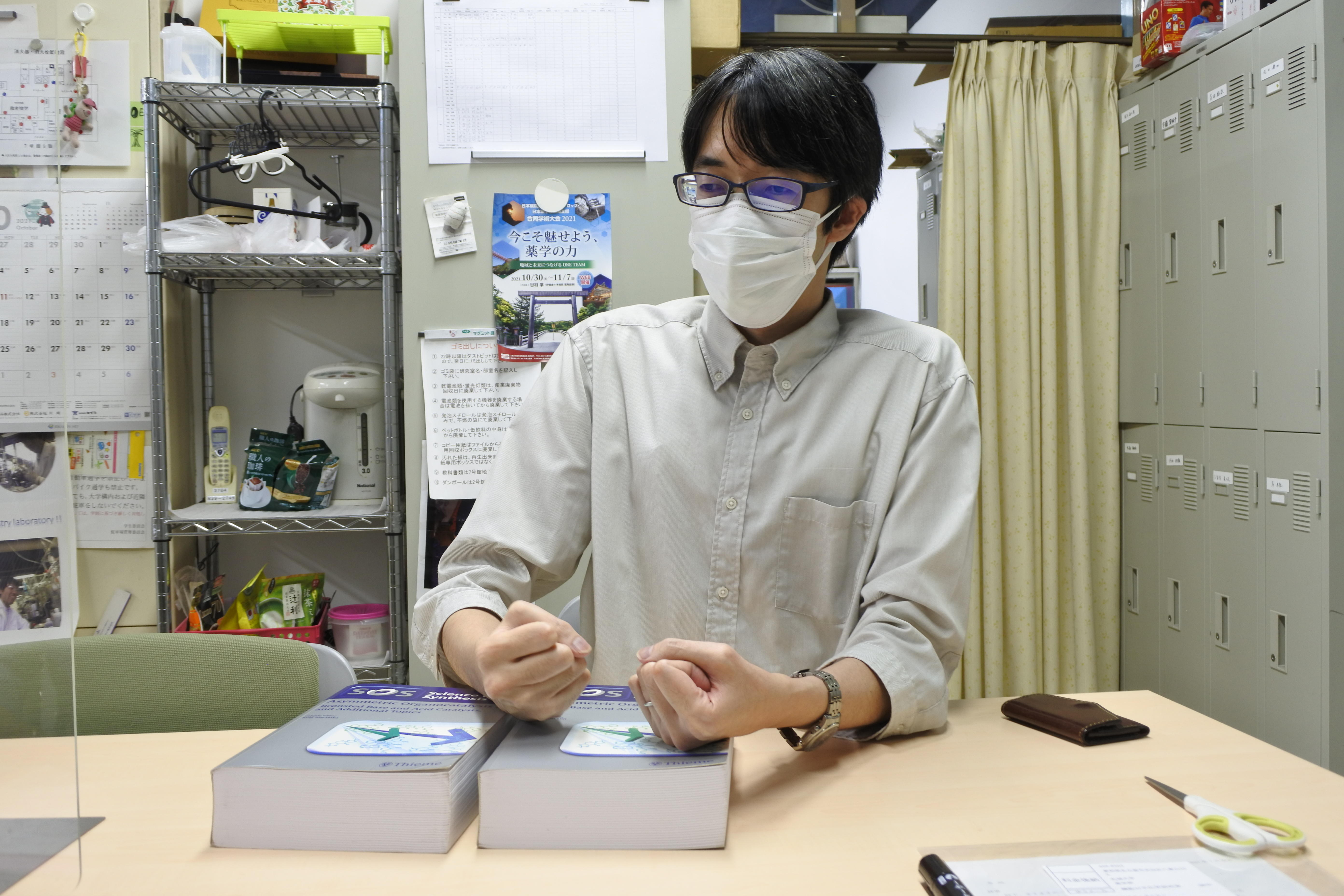 合成化学の分厚い本と取材に答える西川泰弘助教