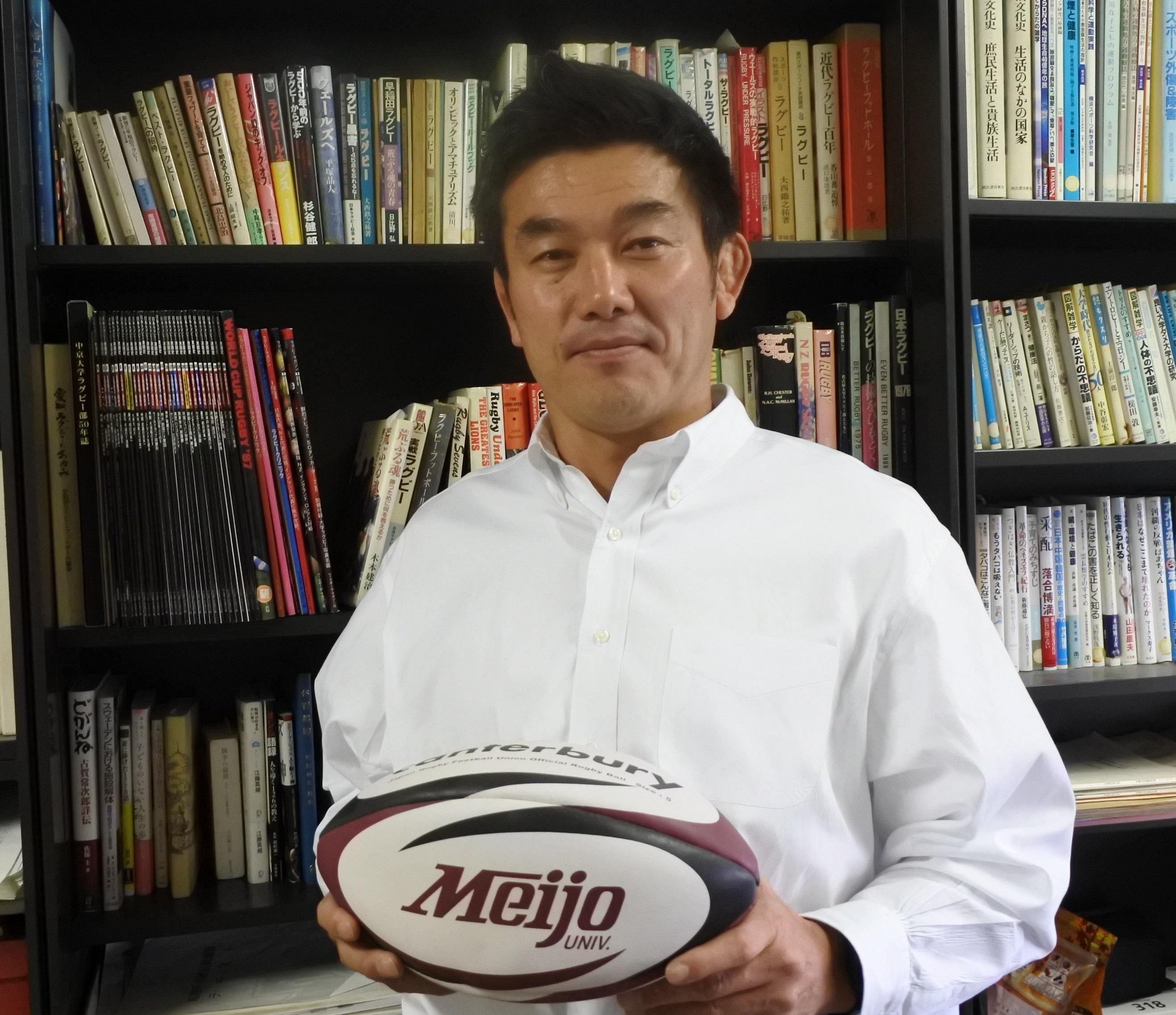 10号館の研究室でラグビーボールを持つ小泉和也准教授
