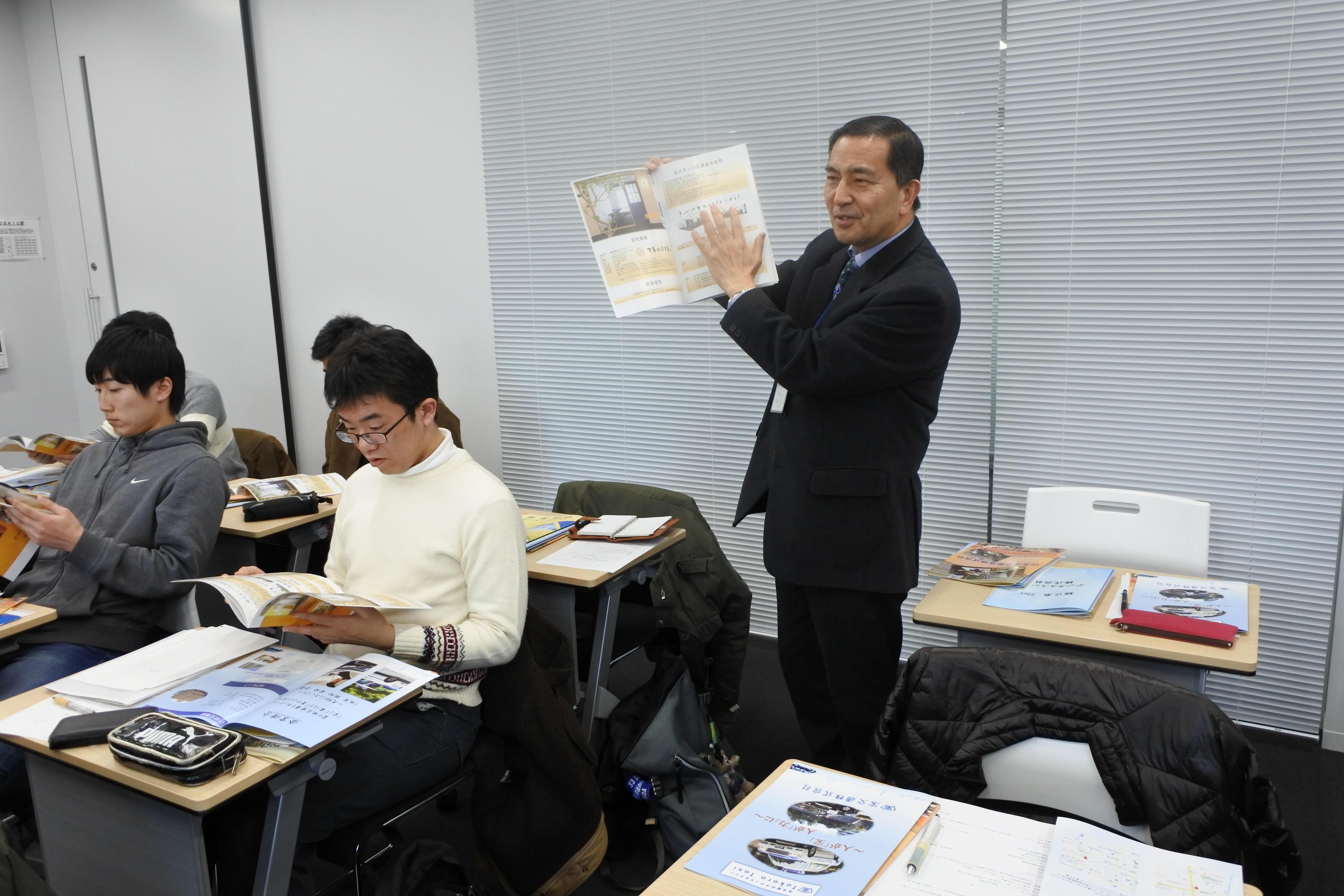 志プロジェクトの発表会で、学生手作りの会社案内の出来栄えを講評する雑賀教授