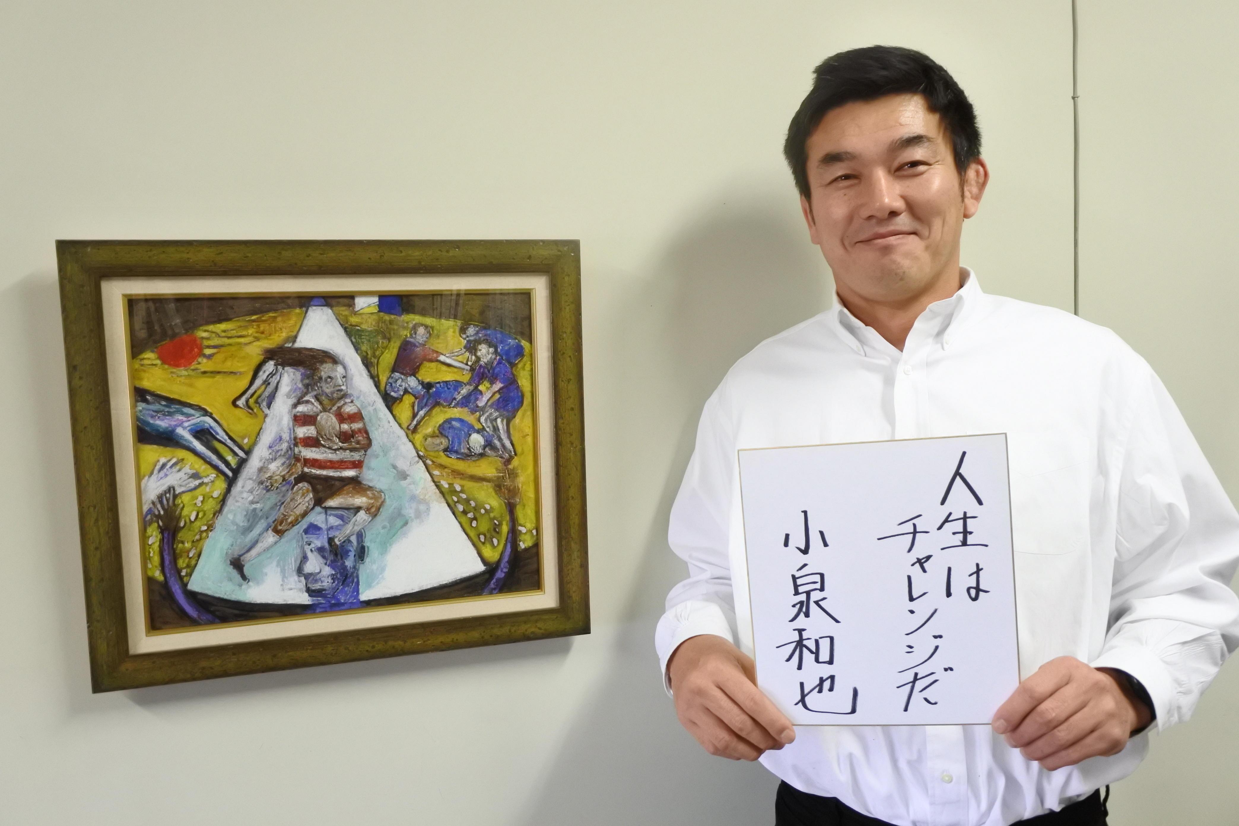 座右の銘を書いた色紙を手にする小泉和也准教授(左は本学卒業生の田村勉さんの絵)