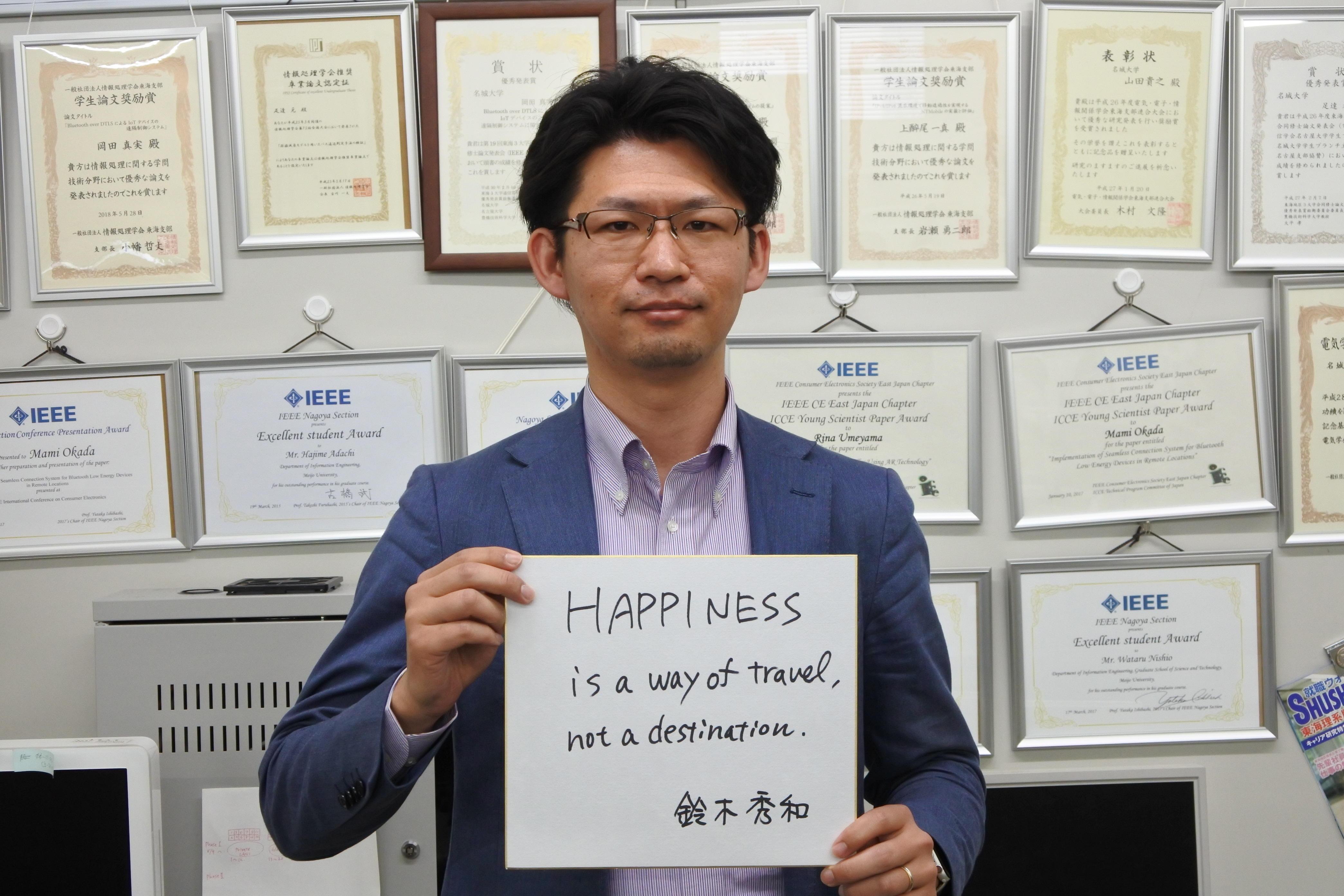 学生の表彰状をバックに色紙を手にする鈴木秀和准教授