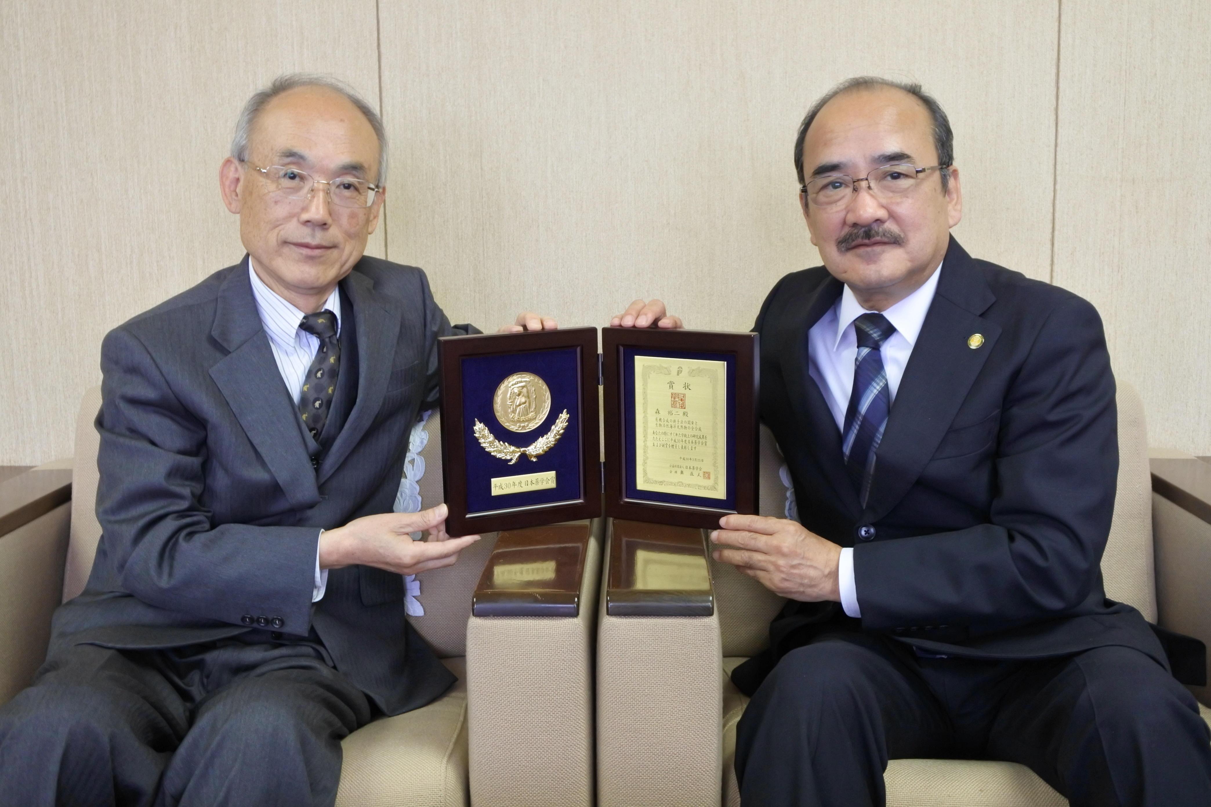 吉久光一学長に薬学会賞の盾を披露した森教授