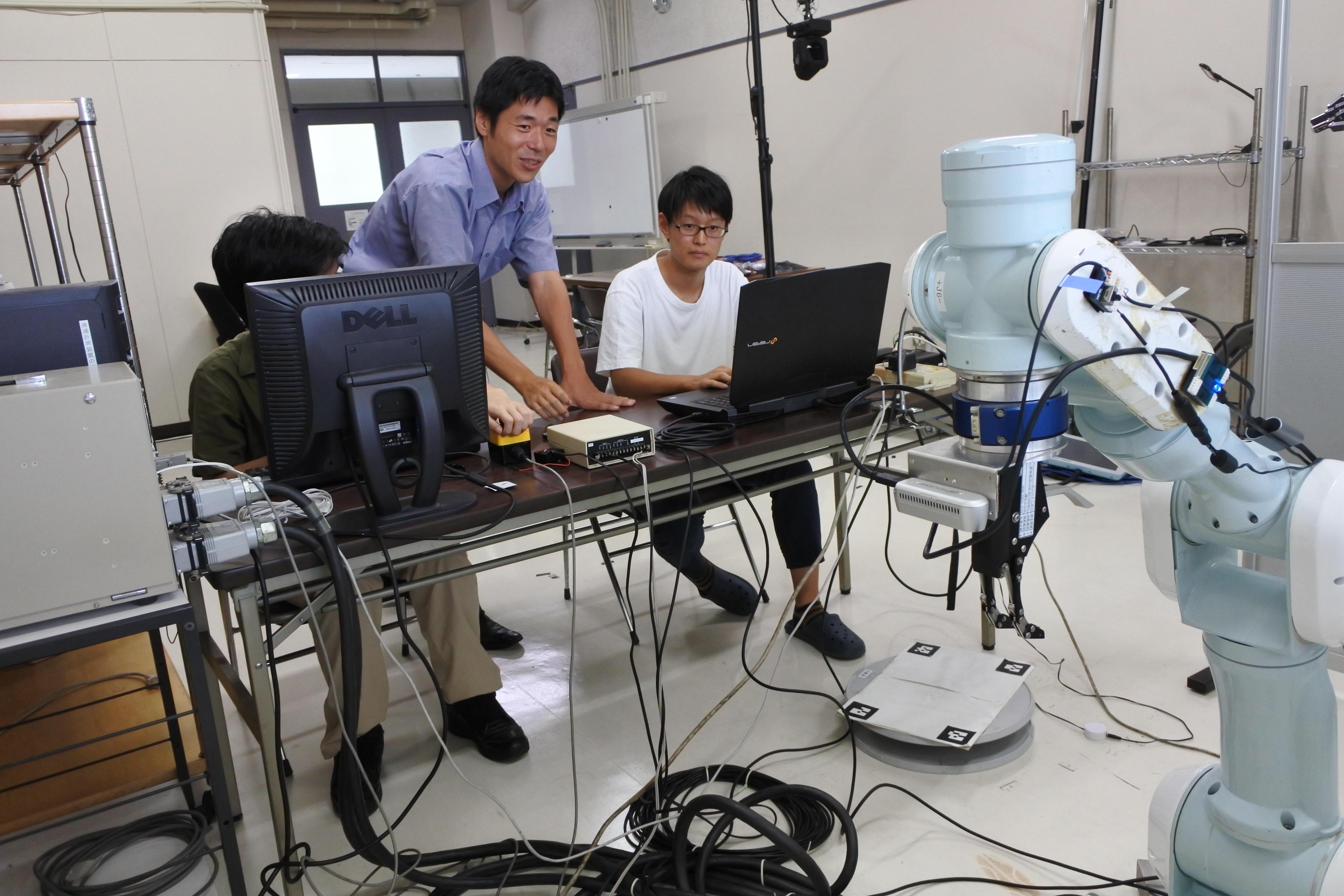 学生のロボットアーム操作を見守る