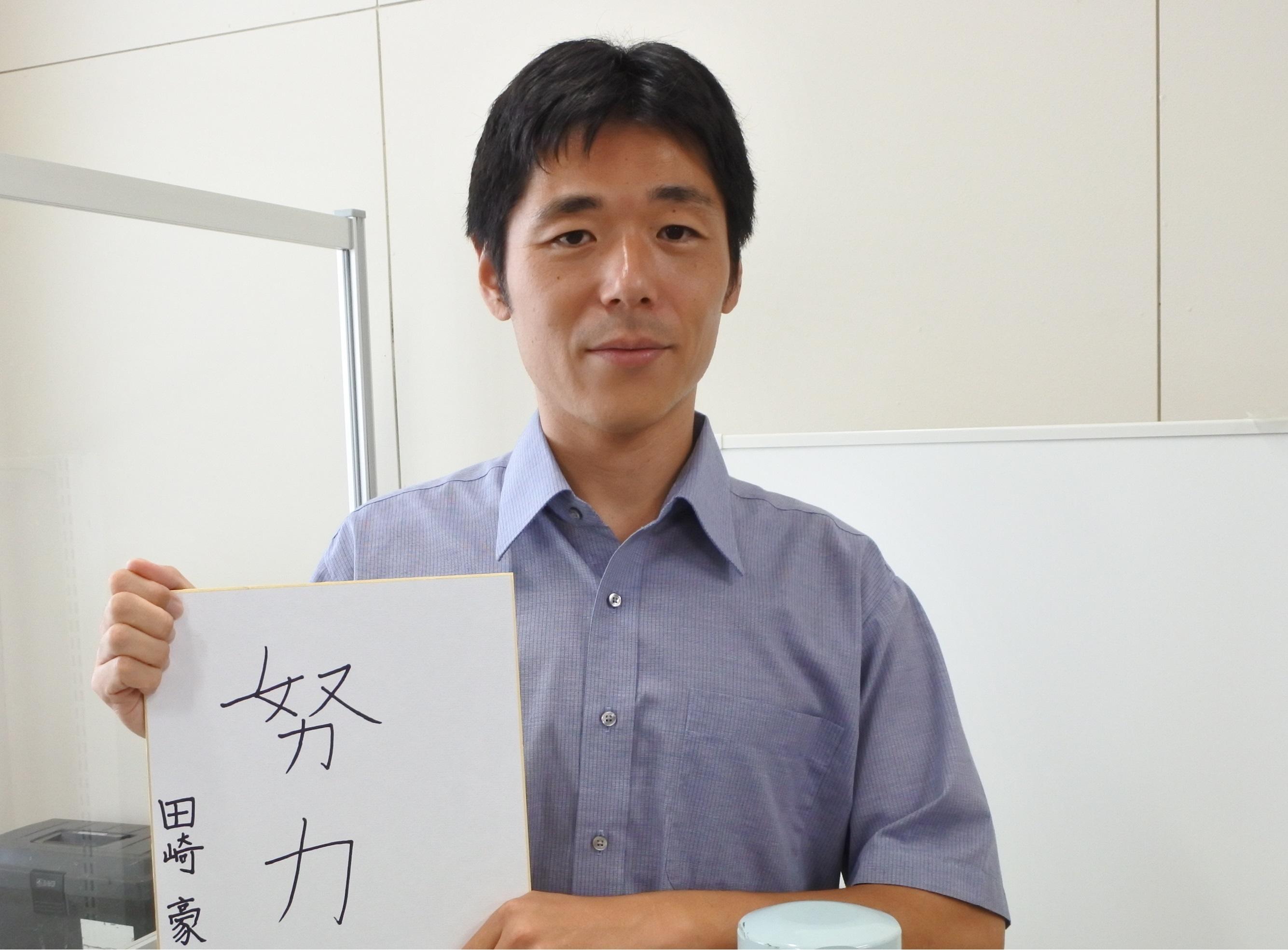 好きな言葉を色紙に書いた田崎准教授