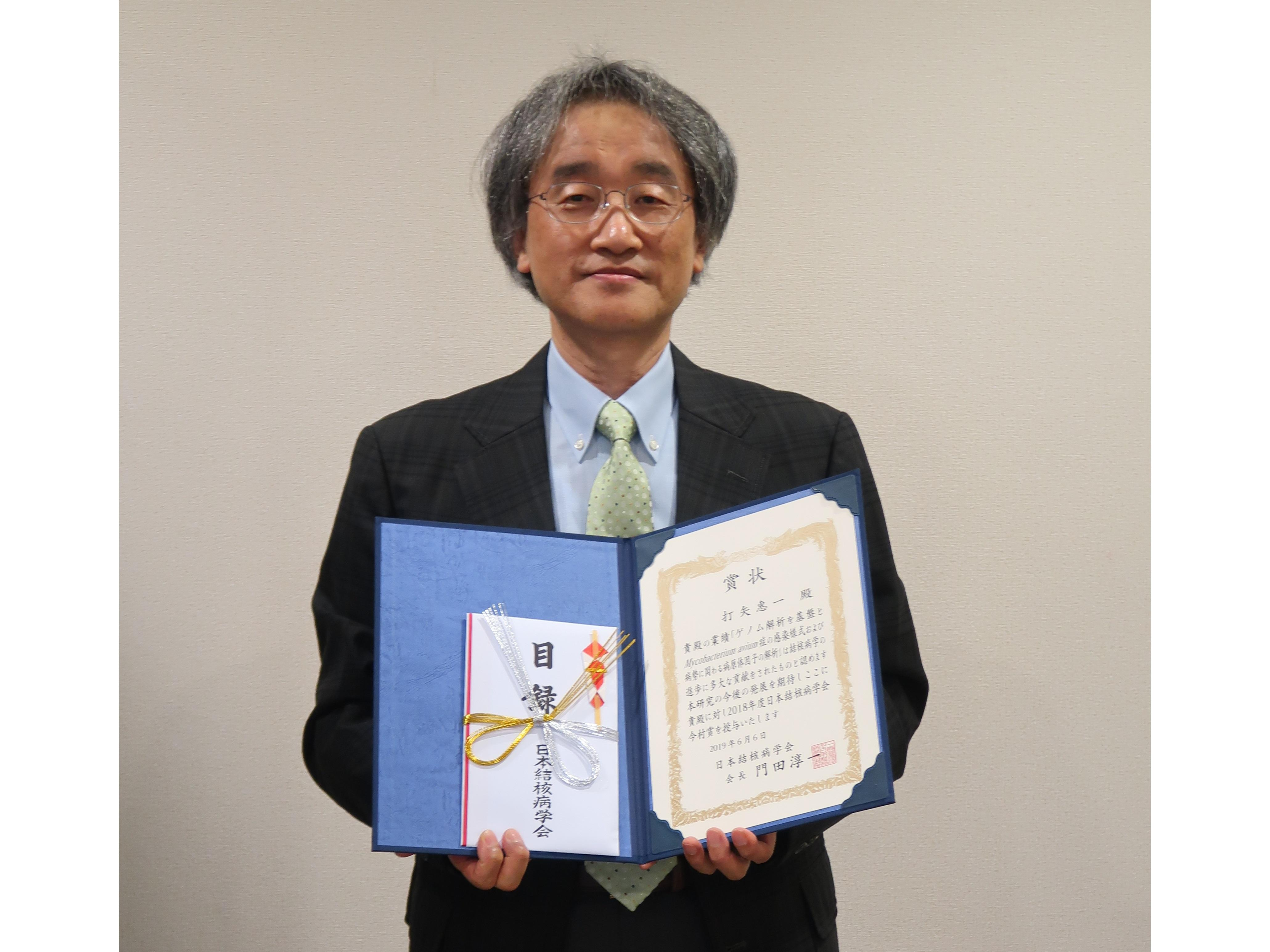 今村賞の賞状を手にする打矢惠一准教授