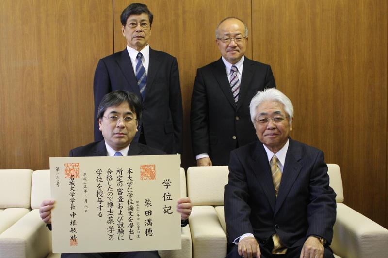 学位授与式を終えた柴田さんと檀上教授(後ろは中根敏晴学長と小嶋仲夫薬学部長)